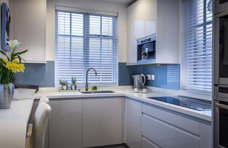 маленькая белая кухня в стиле хай-тек с глянцевыми фасадами и мойкой у окна