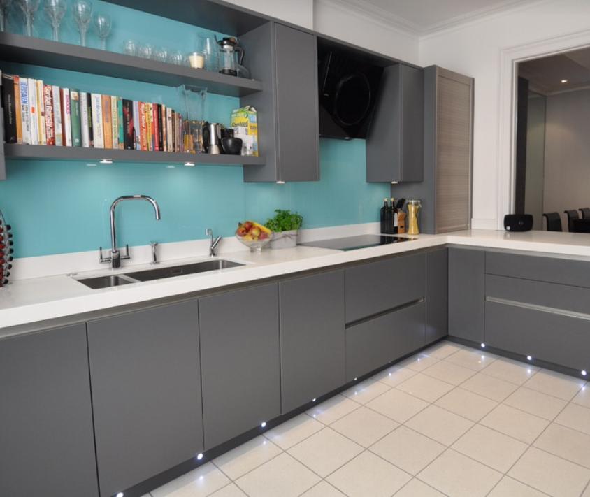 серая кухня модерн с голубым фартуком из стекла