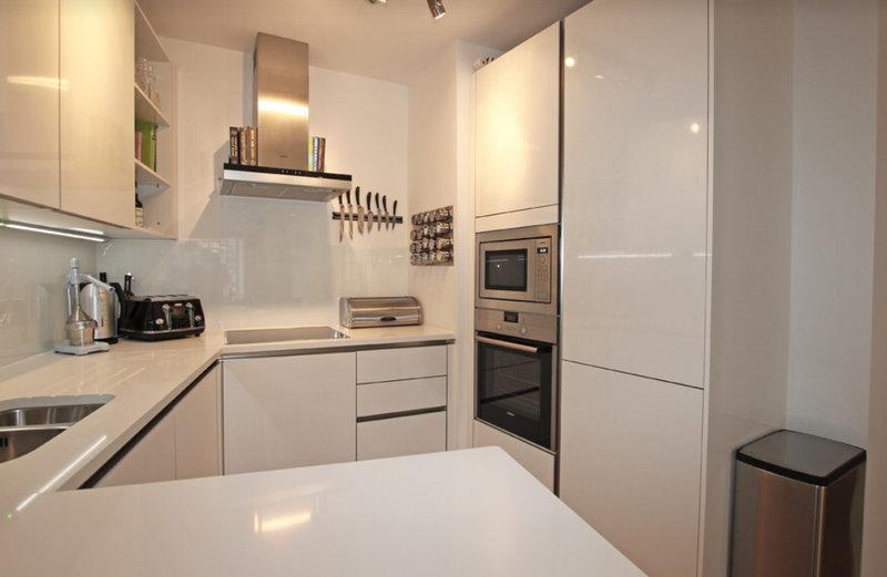 маленькая белая глянцевая кухня со шкафами-пеналами