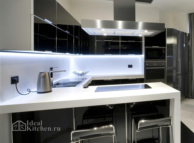 черная кухня хай-тек со стеклянными фасадами и белой каменной столешницей
