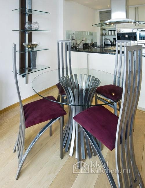 круглый стеклянный стол с необычным подстольем из металла