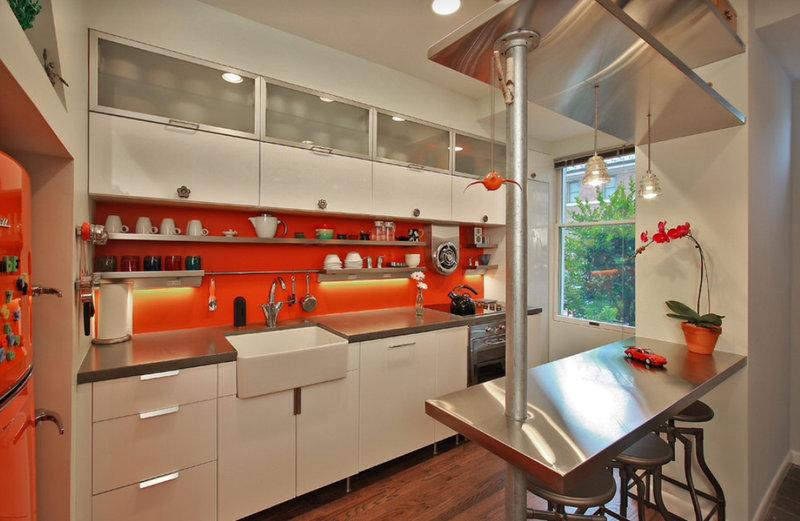 маленькая белая кухня хай-тек с оранжевым фартуком и барной стойкой