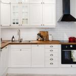 маленькая белая кухня с темной плитой и вытяжкой