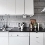 белая кухня с черной столешницей и серым фартуком из плитки под кирпич