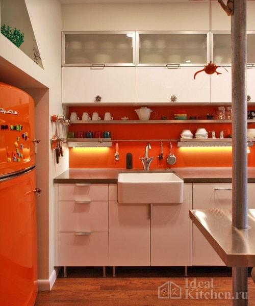 белая кухня с оранжевым фартуком и холодильником