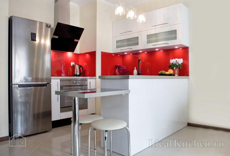 белая п-образная кухня с красным стеклянным фартуком