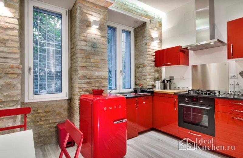 кухня красного цвета с черной столешницей и кирпичными стенами
